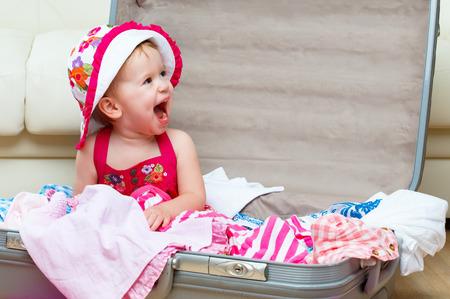 Glückliches Baby Mädchen wird auf einer Reise, packen einen Koffer Standard-Bild - 27756434