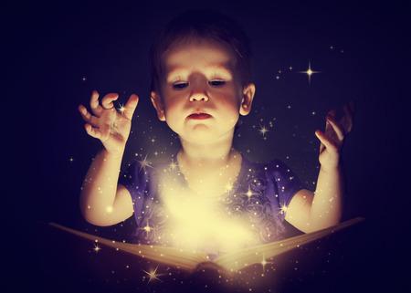 어두운 배경에 마법의 책을 가진 여자 아기 스톡 콘텐츠