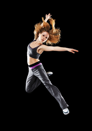 woman dancer dancing modern dance, jump on a black background photo