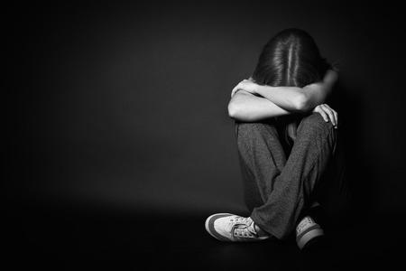 うつ病と黒の背景に暗い上で泣いている絶望の悲しい女