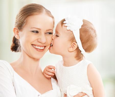 madre y bebe: familia feliz. Madre y bebé juegos de la hija, abrazos, besos en casa en el sofá