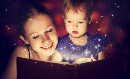 personas leyendo: madre de la familia y el ni�o hija la lectura de libros de magia en la oscuridad Foto de archivo
