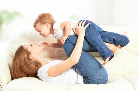 tickling: happy family. Mother and baby daughter plays, hugging, kissing at home on the sofa