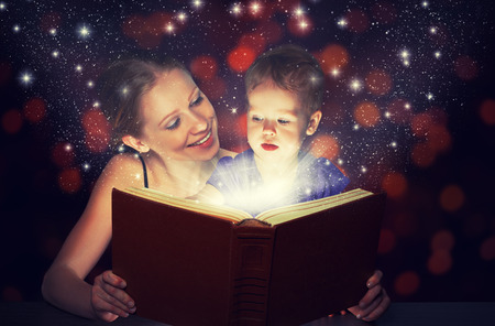 school library: family mother and child baby daughter reading magic book in the dark Stock Photo