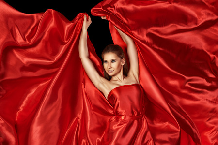 beautiful woman in a red silk dress flying photo