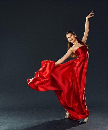 beautiful ballerina dancing a long red dress flying and in pointe photo