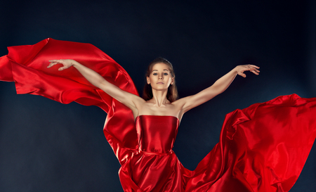 beautiful inspirational woman dancing in a theatrical red silk dress flying photo