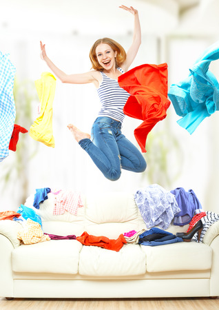 girl clothes: Funny happy girl with flying clothes jumping at home Stock Photo