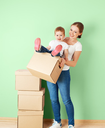 relocating: happy family mother and baby daughter in an empty apartment near the wall with cardboard boxes relocation