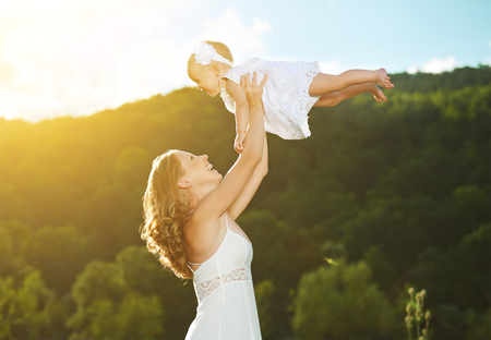 throws: happy family. Mother throws up  baby in the sky in nature Stock Photo