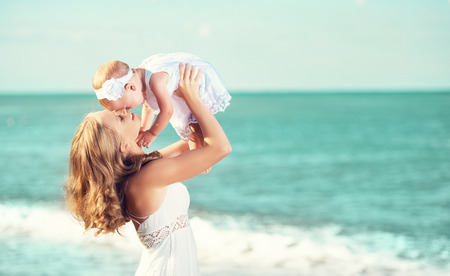 beach kiss: happy familyin white dress. Mother throws up  baby in the sky in beach Stock Photo