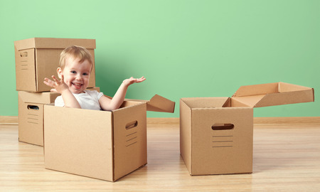carton box: happy baby toddler sitting in a cardboard box empty room
