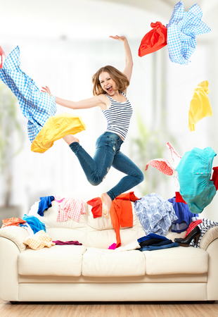 woman closet: Funny happy girl with flying clothes jumping at home Stock Photo