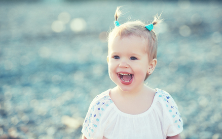 baby hairstyle: Happy baby girl with two tail hairstyle smiling and rejoicing in nature at sea on the beach