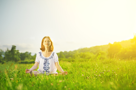 young woman doing yoga, sitting in lotus position on green grass photo