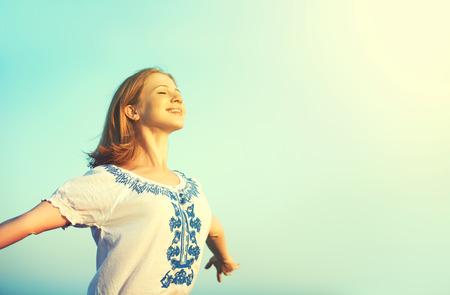 행복 한 젊은 여자는 하늘에 그녀의 팔을 열고 인생을 즐기는