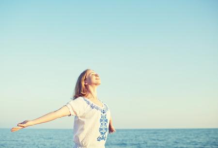 zbraně: šťastná mladá žena otevřít rukama k nebi a moře a užívat si života Reklamní fotografie