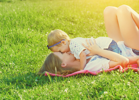 happy family on nature. mom and baby daughter lying are playing and laughing in the green grass