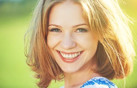 femme qui rit: heureux belle jeune femme en riant et souriant sur la nature en vert