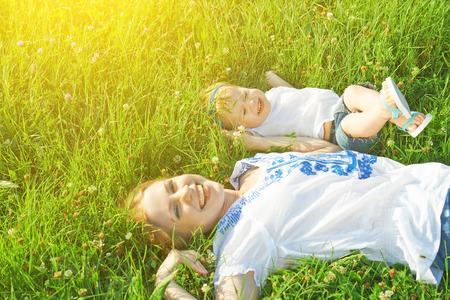 familia feliz en la naturaleza. mamá y el bebé hija acostada están jugando y riendo en la hierba verde