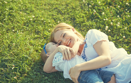 mom baby: happy family on nature. mom and baby daughter lying are playing and laughing in the green grass