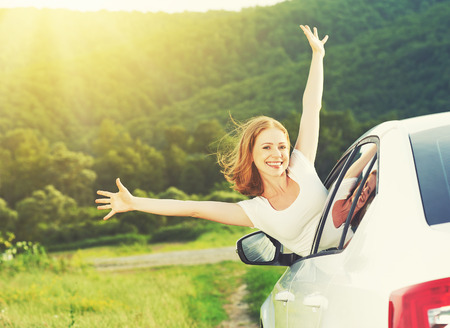 the car window: happy woman looks out the car window on nature summer Stock Photo