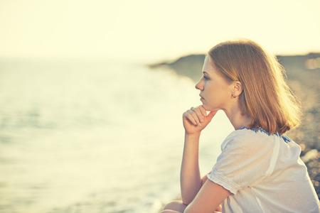 해변에 해안에 앉아 슬픈 소녀는 바다에서 거리에 보이는