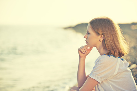 sad girl sitting on the coast on beach and looks into the distance at sea Stock Photo - 29129074