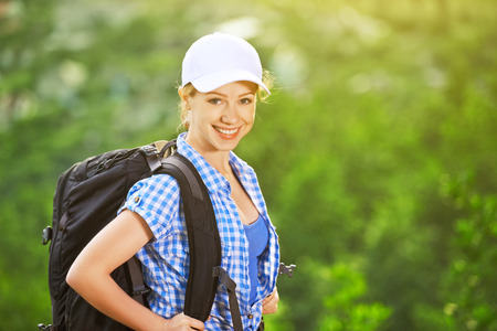 happy woman tourist with a backpack on nature photo