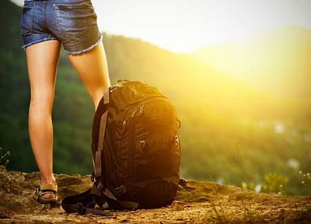 mochila de viaje: las piernas de una mujer turista y mochila de viaje en la cima de la monta�a al atardecer