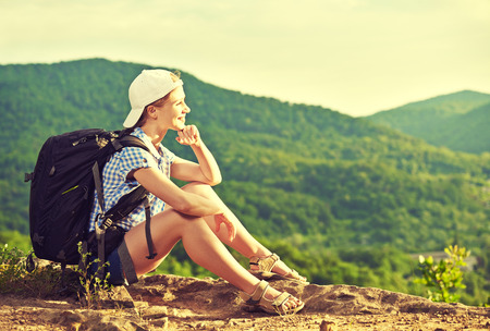 woman tourist with a backpack sitting, resting on a mountain top on a rock on the nature of the journey photo