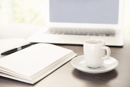netbooks: work office desk with a cup of coffee computer laptop, notebook, pen Stock Photo