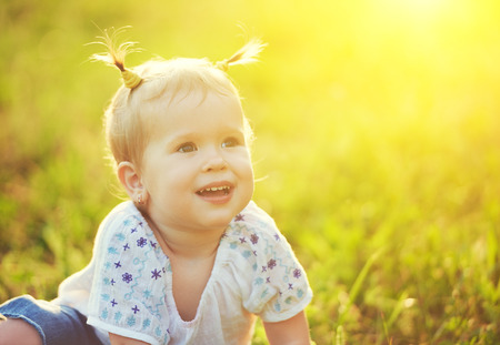 cute blonde: face of a happy beautiful baby girl on nature summer