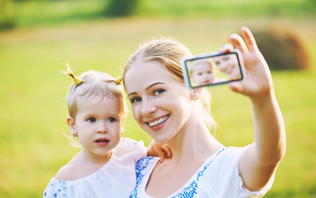 taking photo: other and baby daughter photographing selfie themselves by mobile phone in summer