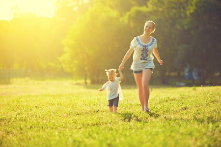happy family on nature walks in the summer. mother and child run on field photo