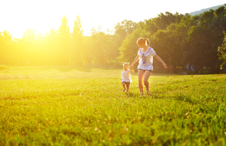 park: happy family on nature walks in the summer. mother and child run on field