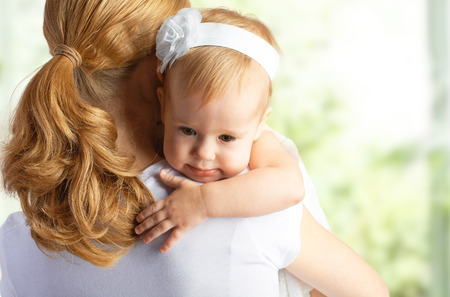 young mother hugging and comforting her baby daughter photo