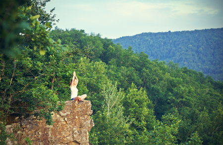 yoga meditation: woman meditating in lotus posture, doing yoga on top of the mountain on a rock in nature in the forest