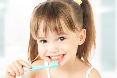 zuby: dentální hygiena. šťastná holčička si čistit zuby