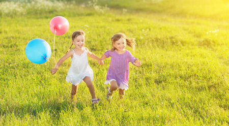 children playing together: happy kids twin sisters running around laughing and playing with balloons in the meadow in summer