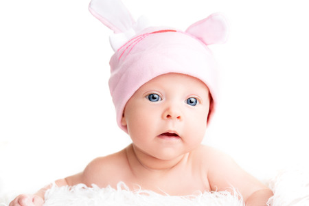 Cute newborn baby girl in a pink hat cap with ears photo