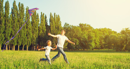 flying kite: happy family in summer nature. Dad and son child flying a kite