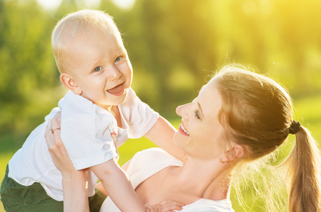 toddler playing: happy family in summer nature. Mom and baby son Stock Photo
