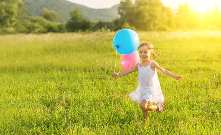 little happy cheerful girl running around playing and having fun with balloons in the summer on the nature