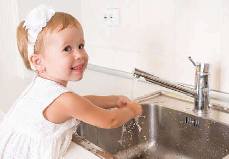 baby girl washes her hands in the bathroom with running water Stock Photo - 30613841