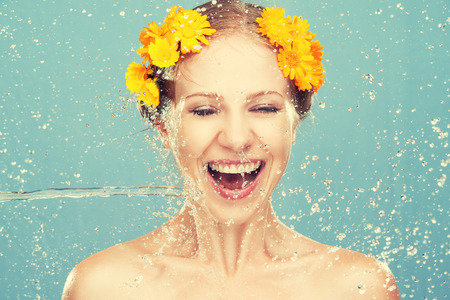 sprays: beauty happy laughing girl with splashes of water and yellow flowers