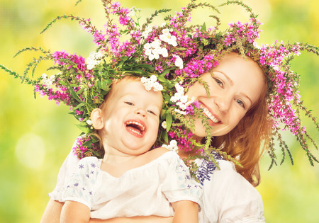 happy laughing family, daughter hugging mother in wreaths of summer flowers in nature photo
