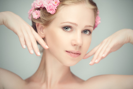 Beauty face of the young beautiful woman with pink flowers in her hair photo