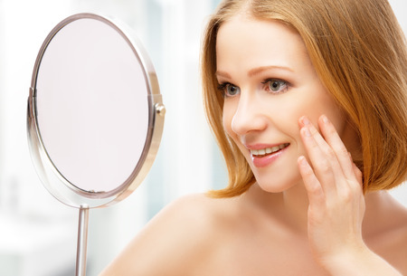 looking: face of young beautiful healthy woman and reflection in the mirror Stock Photo