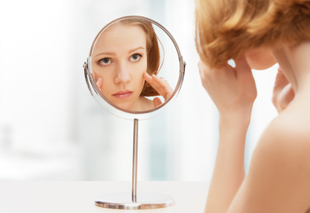 face of young beautiful healthy woman and reflection in the mirror photo